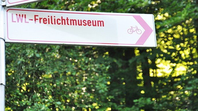A sign of the cycling network showing the way to the museum. On the sign is the inscription LWL open-air museum and a bicycle symbol.