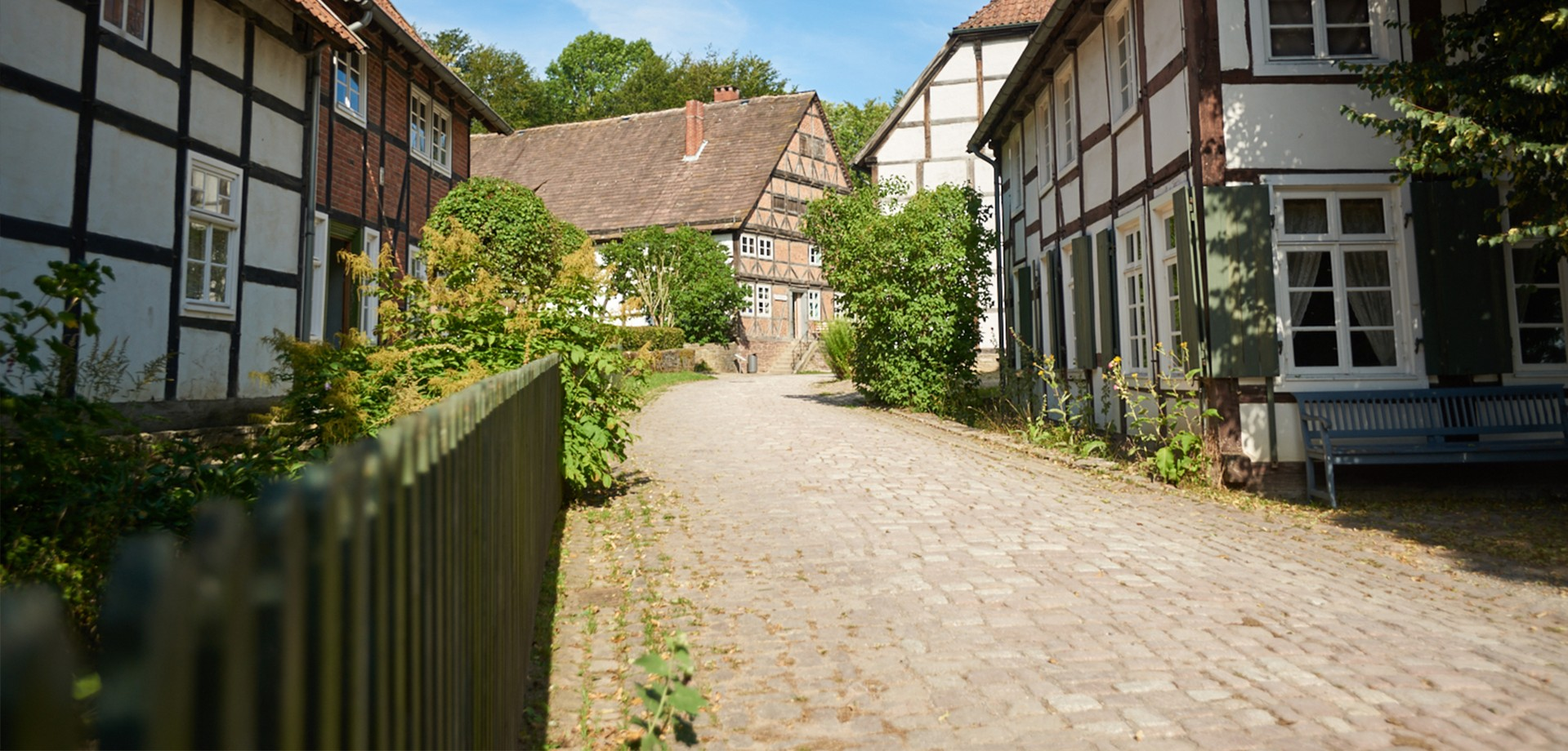 A path in the Paderborn Village between historic buildings.