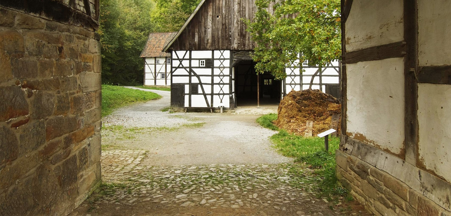 A passage to a farmyard. Straight ahead is a half-timbered house. The passage and the house are a picture of the Gräftenhof.