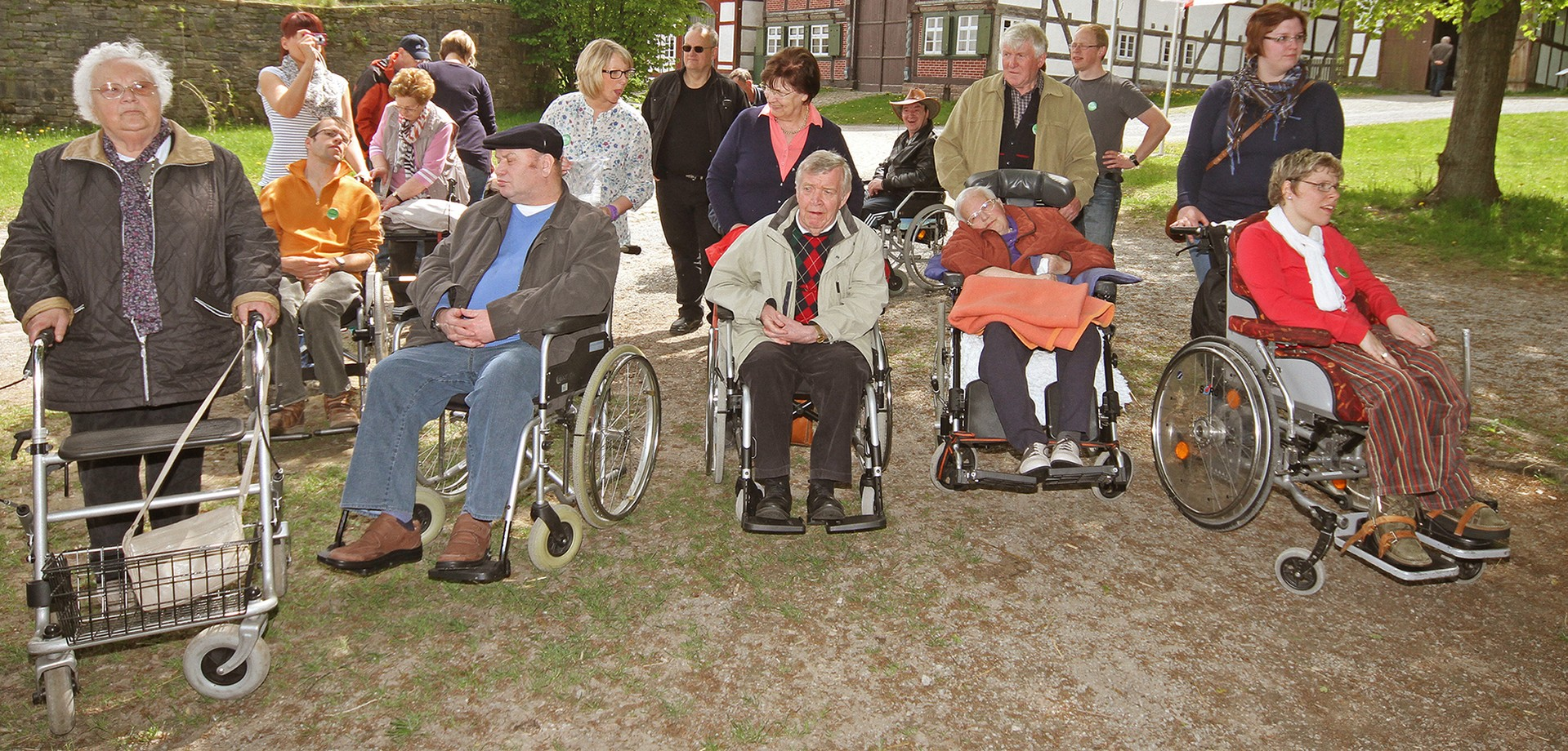 A group of 18 adults. Some are a bit older. Some use a walker or sit in a wheelchair.